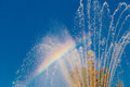 Refraction of light in the spray the fountain and colored rainbow appeared on the background blue sky Royalty Free Stock Images