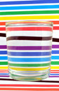 Refraction of the lightin a glass light colored striped backgound Stock Photography