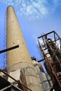Refractory tall brick chimney at a with various machines and equipment Stock Photo