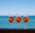 Refreshing aperitif Aperol spritz on a background of blue sea.
