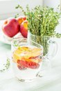 Refreshing fizzy drink with slices of peach a nectarine sprigs thyme on the background the bouquet thyme and fresh fruit Stock Photo