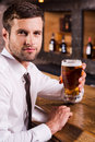 Refreshing with glass of cold beer side view handsome young man in shirt and tie holding and looking at camera while sitting at Stock Image