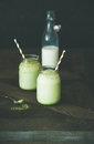 Refreshing iced coconut matcha latte drink in jars, copy space