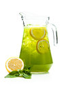 Refreshing punch pitcher with a drink basil with lemon slices on white background Royalty Free Stock Images