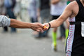 Refreshment hand of a volunteer giving a sponge at a point in a marathon race to an athlete with the two hands coming together Royalty Free Stock Image