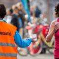 Refreshment hand of a volunteer holding a can of water at a point in a marathon race to an athlete with a runner passing by Royalty Free Stock Photos