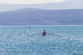 Regatta rowing race teenager endurance fitness male completes single skulls canoe time trial Royalty Free Stock Images