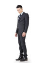 Regret young business man standing and thinking full length portrait isolated on white background Royalty Free Stock Photography