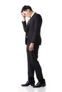 Regret young business man standing and thinking full length portrait isolated on white background Royalty Free Stock Images