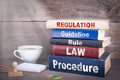 Regulation concept. Stack of books on wooden desk Royalty Free Stock Photo