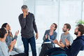 Rehab group applauding delighted man standing up men at therapy session Stock Photo