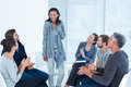 Rehab group applauding delighted woman standing up women at therapy session Royalty Free Stock Image