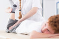 Rehabilitation is a tedious process female physiotherapist exercising the leg of her young patient Stock Photos