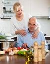 Reife frau mit älterem älterem vorbereitendem vegetarischem lebensmittel Stockbild
