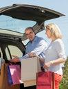 Reifer ehemann und frau die in einkaufstaschen eines autos sich setzt Lizenzfreies Stockfoto