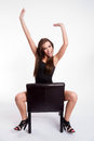 Rejoicing young beautiful barefoot woman straddles black leather shot from above straddling common chair celebrating Royalty Free Stock Photo