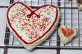 Relationship pair of heart sugar cookies with white frosting and red sprinkles. representing relationship. Royalty Free Stock Photo