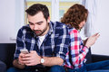 Relationship and phone addiction concept young couple using th their smart phones at home Royalty Free Stock Photography