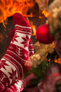 Relax in christmas ambiance somebody relaxing next to fireplace and tree wearing a cute winter socks Royalty Free Stock Photography