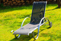 Relax. Empty deck chair on grass in garden. Royalty Free Stock Photo