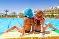 Relax on holidays at swimming pool of two tanned girls Stock Image