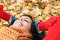 Relax and peace on happy autumn woman season brunette girl lying down smiling fall golden leaves in park tranquility Royalty Free Stock Photography
