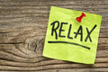 Relax reminder note handwriting on a green sticky against grained and knotted wood board Royalty Free Stock Photography