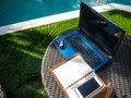 Relax time working area near pool with laptop, notebook and phone Royalty Free Stock Photo