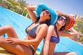 Relax of two tanned girls at swimming pool Stock Photo