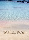 Relax word written in the sand on a beautiful beach with clear blue waves in background Stock Photo