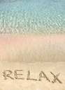 Relax word written in the sand on a beautiful beach with clear blue waves in background Royalty Free Stock Image
