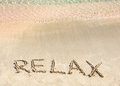 Relax word written in the sand on a beautiful beach with clear blue waves in background Stock Image