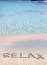 Relax word written in the sand on a beautiful beach with clear blue waves in background Stock Photography