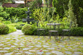 Relaxation area in a English garden. Chair with blurry fountain Royalty Free Stock Photo