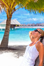 Relaxation on the beach cute blond girl leaned palm tree and looking sun through sunglasses summer time vacation leisure concept Royalty Free Stock Image