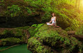 Relaxation in forest at the Waterfall. Ardha Padmasana pose Royalty Free Stock Photo