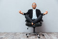 Relaxed african young man sitting and meditating on office chair Royalty Free Stock Photo