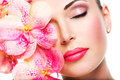 Relaxed beautiful face of a young girl with clear skin and pink orchids beauty treatment concept Royalty Free Stock Photo