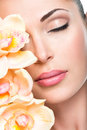 Relaxed beautiful face of a young girl with clear skin and pink orchids beauty treatment concept Royalty Free Stock Images