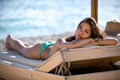 Relaxed beautiful woman sunbathing in a bikini on a beach at tropical travel resort,enjoying summer holidays.SPF protection Royalty Free Stock Photo