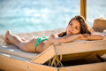 Relaxed beautiful woman sunbathing in a bikini on a beach at tropical travel resort enjoying summer holidays spf protection young Royalty Free Stock Photography