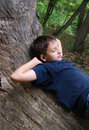 Relaxed boy on the old trunk Royalty Free Stock Images