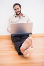 Relaxed businessman sitting on the floor while using laptop in living room Royalty Free Stock Photo