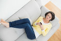 Relaxed casual brunette in yellow cardigan texting with a mobile phone lying on couch bright living room Royalty Free Stock Images