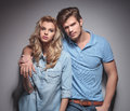 Relaxed casual couple lookig at the camera while posing in studio Stock Images
