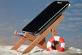 Relaxed cellular phone a is relaxing in a sunny beach scenery Stock Photo