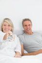 Relaxed couple watching tv in bed at home bedroom Stock Photo