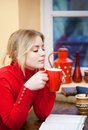 Relaxed cute blond portrait of a girl with a cup of hot beverage Stock Photography