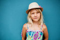Relaxed cute young girl portrait of in pose wearing stylish hat outside against blue wall background Stock Photos