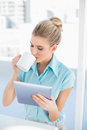 Relaxed elegant woman using tablet while drinking coffee in bright office Royalty Free Stock Images